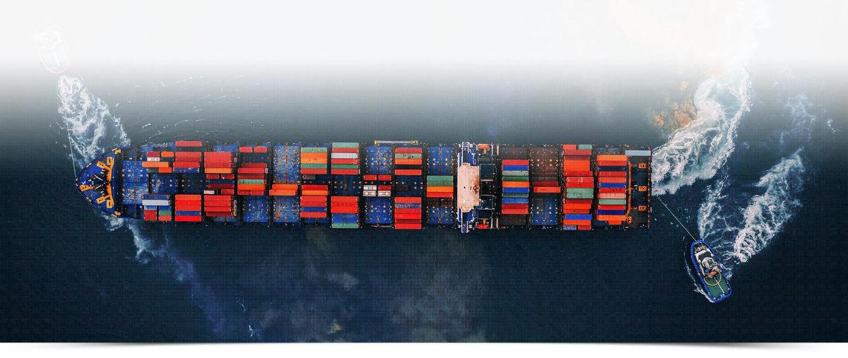 manewrujący kontenerowiec wraz z holownikami baner